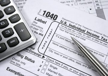 1040 tax form, pen and calculator